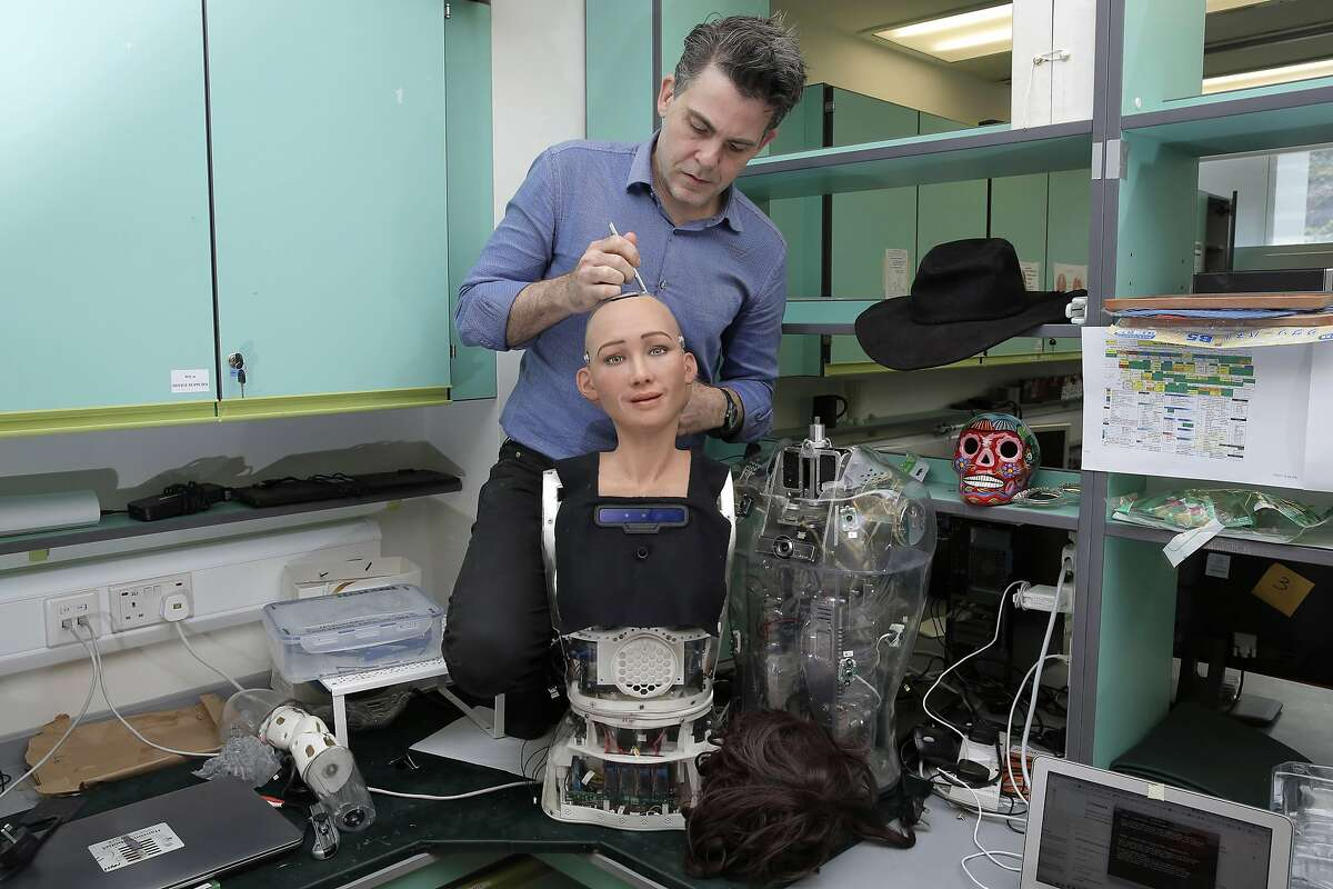 In this Sept. 28, 2017, photo, David Hanson, the founder of Hanson Robotics, works on his company's flagship robot Sophia, a lifelike robot powered by artificial intelligence in Hong Kong. Sophia is a creation of the Hong Kong-based startup working on bringing humanoid robots to the marketplace. Hanson envisions a future in which AI-powered robots evolve to become �super-intelligent genius machines� that can help solve mankind�s most challenging problems. (AP Photo/Kin Cheung)