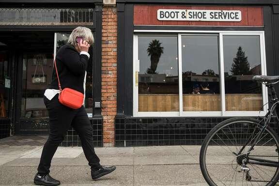 A woman walks past Boots & Shoe Service Thursday, Jan. 18, 2018 in Oakland, Calif.