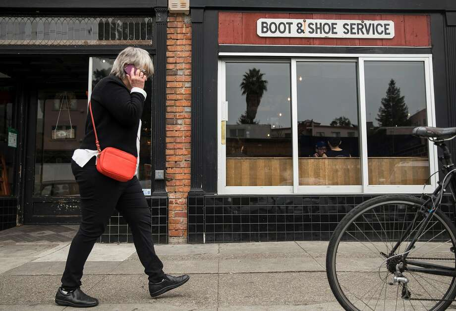 A woman walks past Boots & Shoe Service. Photo: Jessica Christian / The Chronicle