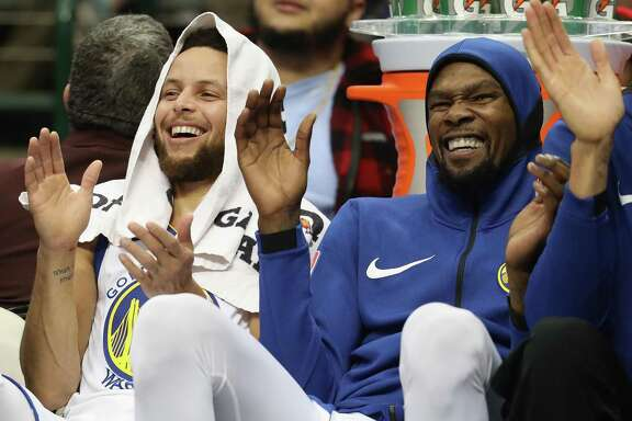Stephen Curry #30 and Kevin Durant #35 of the Golden State Warriors share a laugh during play against the Dallas Mavericks at American Airlines Center on January 3, 2018 in Dallas, Texas.