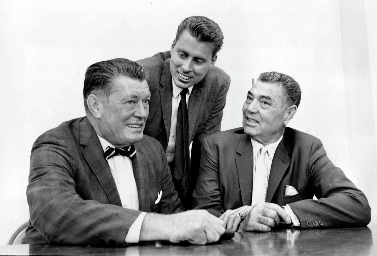In this Sept. 23, 1964 file photo, boxing heavyweights Gene Tunney, left, and Jack Dempsey, right, pose with Tunney's son, John Tunney, at a news conference in Los Angeles, California, on Sept. 23, 1964.