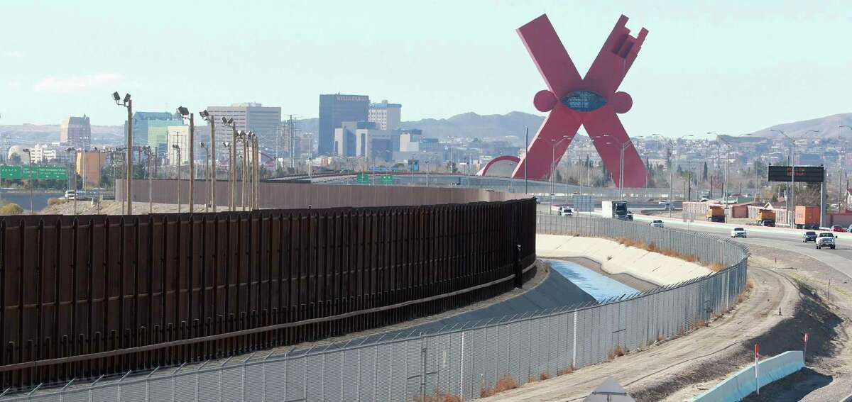 Traffic moves on the El Paso border highway, right, next to the border fence which separates the U.S. and Mexico.
