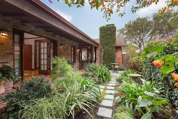 The garden features a covered brick patio and established plantings.