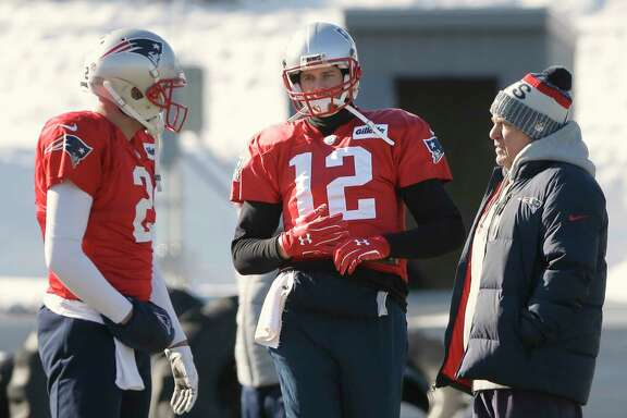New England Patriots quarterbacks Tom Brady, center, missed practice after suffering an injury to his right hand when a teammate ran into him during a handoff in practice Wednesday.