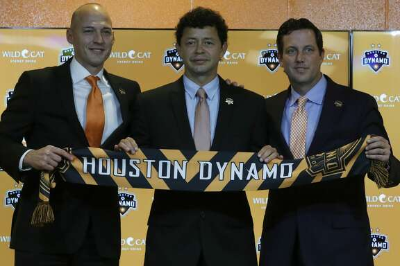 Matt Jordan, Vice President/General Manager of the Houston Dynamo with Wilmer Cabrera, center, introduced as the new head coach and Chris Canetti President, hold up a scarf during the press conference at BBVA Compass Friday,Oct. 28, 2016 in Houston.   ( Karen Warren / Houston Chronicle )