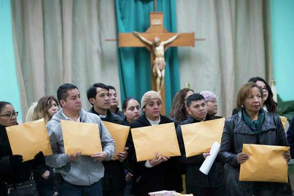 Members of the community and clergy hold envelopes with postcards addressed to legislators asking them to support Deferred Action for Childhood Arrivals (DACA) recipients and keep families together. More than 20,000 postcards are being sent. Thursday, Jan. 18, 2018, in Houston. ( Marie D. De Jesus / Houston Chronicle )