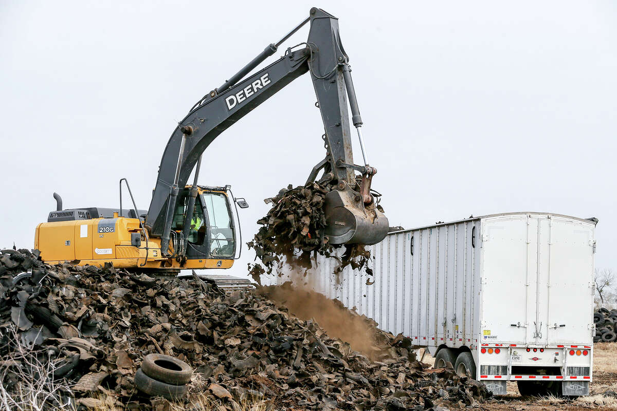 """A trackhoe loads shredded tires onto a waiting truck at the infamous """"Safe Tire"""" site at 11150 Applewhite Road in San Antonio on Thursday, Jan. 18, 2018. Nearby Copart Inc. purchased the property in December with the intenion of removing the tires and expanding their operation to the site. An estimated 2,000,000 tires were at the site, though just under 1,000,000 currently remain. Removal of the tires will alleviate the threat of fire and mosquito-borne diseases to San Antonio residents. Copart estimates the tires will be removed by May or June of this year, far short of the 300 days alloted by the Texas Commission on Environmental Quality, at an estimated cost of $2.8 million. MARVIN PFEIFFER/mpfeiffer@express-news.net"""