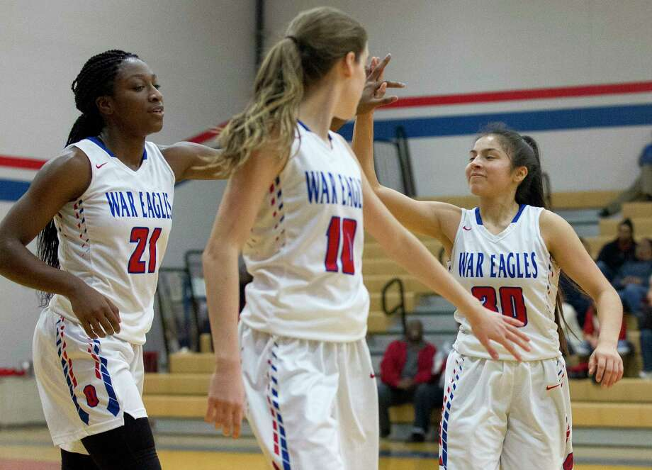 Oak Ridge small forward Alecia Whyte (21) gets a high-five from guard Alyssa Gonzales (30) as guard Maddie Morris (10) looks on during the third quarter of a non-district high school girls basketball game at Oak Ridge High School, Friday, Dec. 8, 2017. Photo: Jason Fochtman, Staff Photographer / © 2017 Houston Chronicle