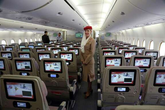 A flight attendant is on duty in an Emirates A380 aircraft, the world's largest passenger airline. Emirates said in a statement Thursday that it put in a $16 billion order for up to 36 of the planes.