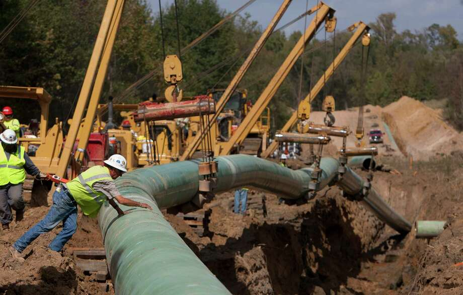 Crewmen work on TransCanada's Keystone XL project near Winnsboro in Wood County in 2012.  Continue to see photos from past protests against the Keystone XL project. Photo: Cody Duty, Staff / Ã  2012 Houston Chronicle