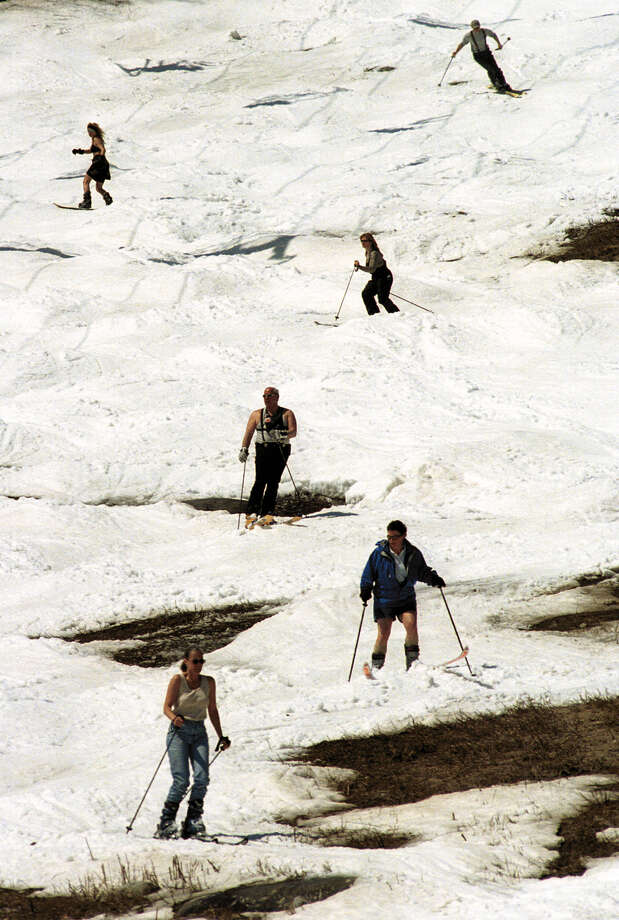 Skiers navigate bare spots on a trail on Little Whiteface Mountain during the final day of skiing at Whiteface in Wilmington, N.Y., Tuesday, May 1, 2001. With morning tempertaures in the upper 70s, Tuesday marked the first time chair lifts operated in May at the resort. (AP Photo/Press-Republican, Mike Dowd) Photo: MIKE DOWD / PRESS-REPUBLICAN