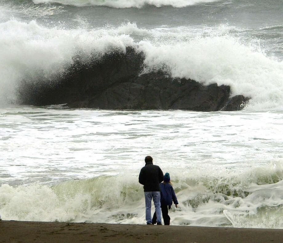 In this Nov. 28, 2001, file photo, beachcombers watch as storm-tossed waves crash over rocks near Depoe Bay, Oregon. A man was swept out to sea near Depoe Bay on Thursday, Jan. 18, 2018. Photo: Don Ryan/AP