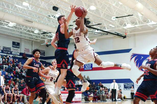 Clear Creek's Nate Jackson (12) drives to the basket past Clear Lake's Riley Abercrombie (11) Thursday, Jan. 18 at Clear Lake High School.