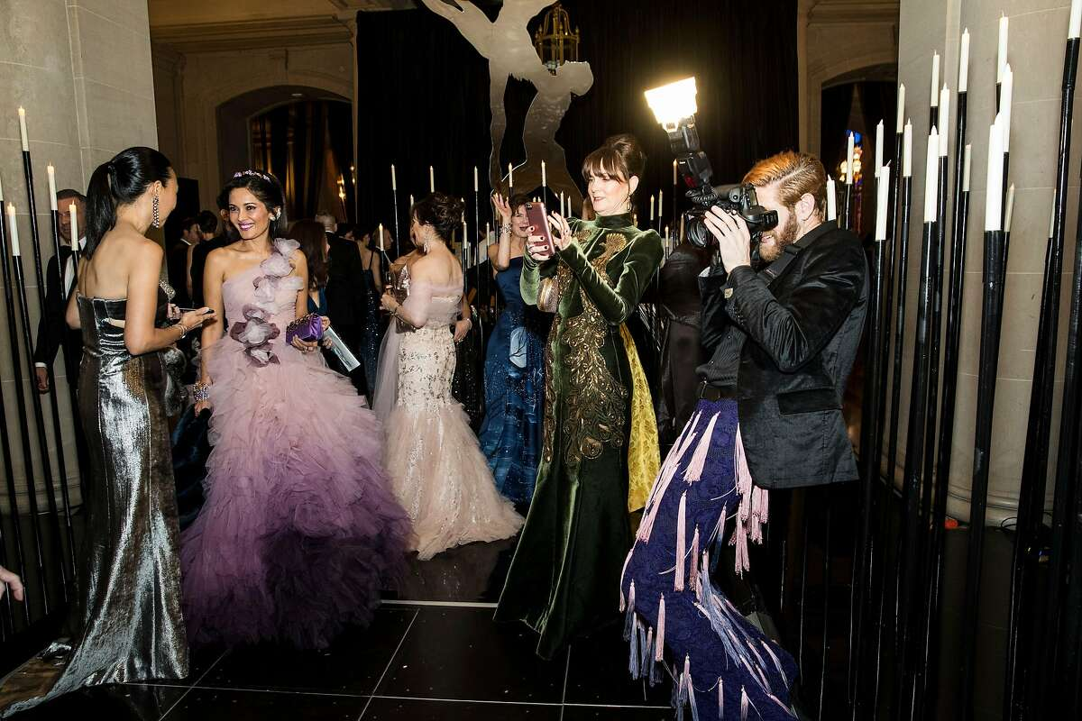 Dr. Carolyn Chang chats with Komal Shah as Allison Speer and Devlin Shand (left to right) take photographs during the cocktail hour at the San Francisco Ballet Opening Night Gala at City Hall in San Francisco, Calif., on Thursday, January 18, 2018.