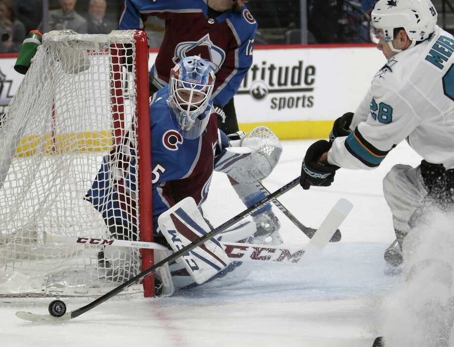 Sharks right wing Timo Meier (right) gathers the puck next to the watchful Avalanche goaltender Jonathan Bernier (45). Photo: Joe Mahoney, Associated Press