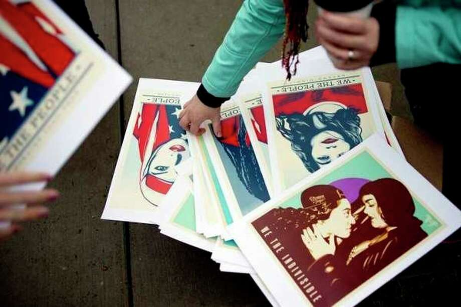 FILE --Protesters pick out posters before the Midland Sister 'Women's March' to protest President Donald Trump on Jan. 21, 2017. Hundreds marched along both sides of of Saginaw Road between Eastlawn Drive and Washington Street during the event which was held to coincide with the 'Women's March on Washington' in Washington, D.C.