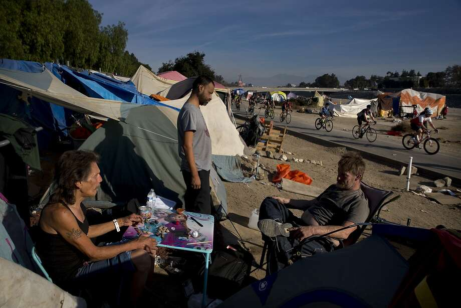 David Pirate, from left, Richard Ramirez, and Eric Koehler, who are homeless, pass time outside their tents after emptying a bottle of vodka as a group of cyclists ride along the Santa Ana River trail Saturday, Dec. 2, 2017, in Anaheim, Calif. Advocates say the homeless population has become more visible as police have cracked down on rules barring camping, driving people from parks and bus benches to a few centralized locations, such as the flood control channel along the Santa Ana River in Anaheim. (AP Photo/Jae C. Hong) Photo: Jae C. Hong, Associated Press