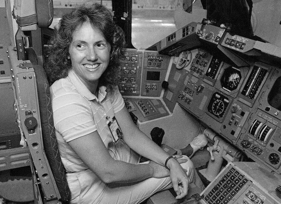 FILE - In this Sept. 13, 1985 file photo, Christa McAuliffe tries out the commander's seat on the flight deck of a shuttle simulator at the Johnson Space Center in Houston, Texas. Thirty-two years after the Challenger disaster, a pair of teachers turned astronauts on the International Space Station will pay tribute to McAuliffe by carrying out her science classes. Photo: RC, AP / AP1985