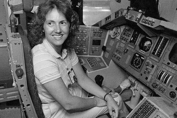 FILE - In this Sept. 13, 1985 file photo, Christa McAuliffe tries out the commander's seat on the flight deck of a shuttle simulator at the Johnson Space Center in Houston, Texas. Thirty-two years after the Challenger disaster, a pair of teachers turned astronauts on the International Space Station will pay tribute to McAuliffe by carrying out her science classes.