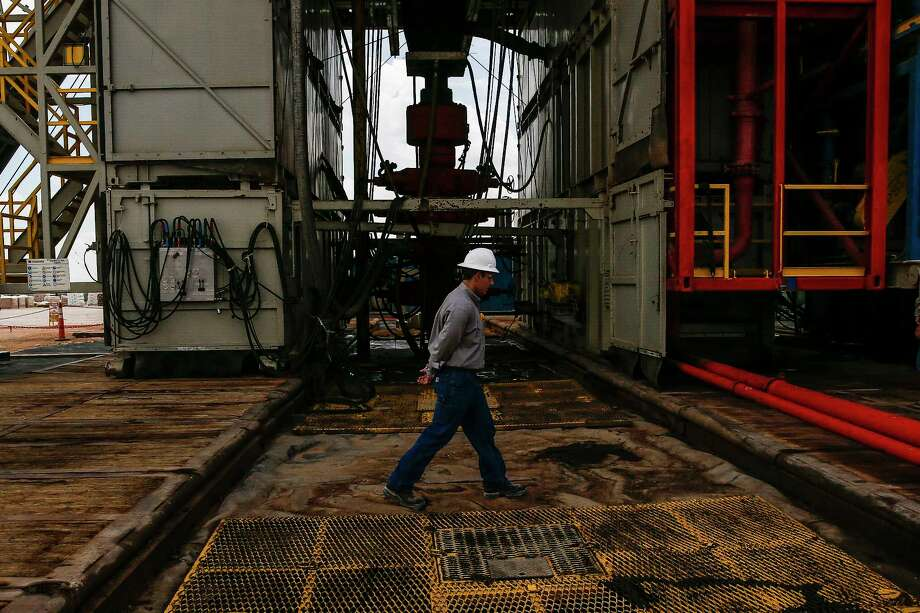 A worker walks across a pad site where a drilling rig will create three to six wells next to each other at a Chevron drilling and hydraulic fracturing site Wednesday, July 19, 2017 in Midland. ( Michael Ciaglo / Houston Chronicle ) Photo: Michael Ciaglo, Staff / Michael Ciaglo
