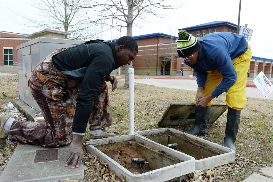 Beaumont utilities workers Jacoby Turner, left, and Joshua Briggs check the water meter outside of Charlton-Pollard Elementary School on Thursday. Students were taken to South Park Middle School for the day due to low water pressure.  Photo taken Thursday 1/18/18 Ryan Pelham/The Enterprise Photo: Ryan Pelham / ©2017 The Beaumont Enterprise/Ryan Pelham
