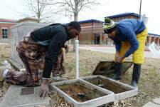 Beaumont utilities workers Jacoby Turner, left, and Joshua Briggs check the water meter outside of Charlton-Pollard Elementary School on Thursday. Students were taken to South Park Middle School for the day due to low water pressure.  Photo taken Thursday 1/18/18 Ryan Pelham/The Enterprise