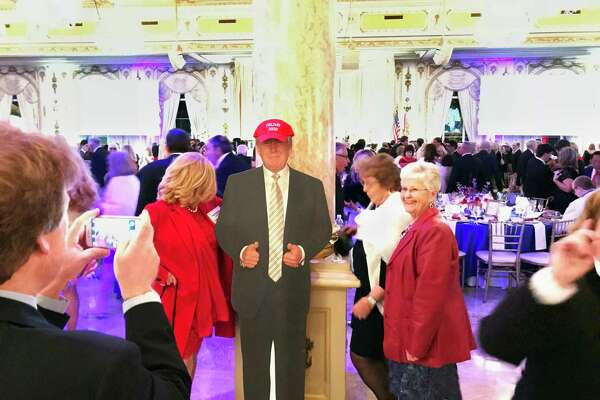 Supporters of President Trump pose with a cardboard cutout at the entrance to the Donald J. Trump Grand Ballroom at Trump's Mar-a-Lago Club in Palm Beach, Fla., on Jan. 18, 2018.