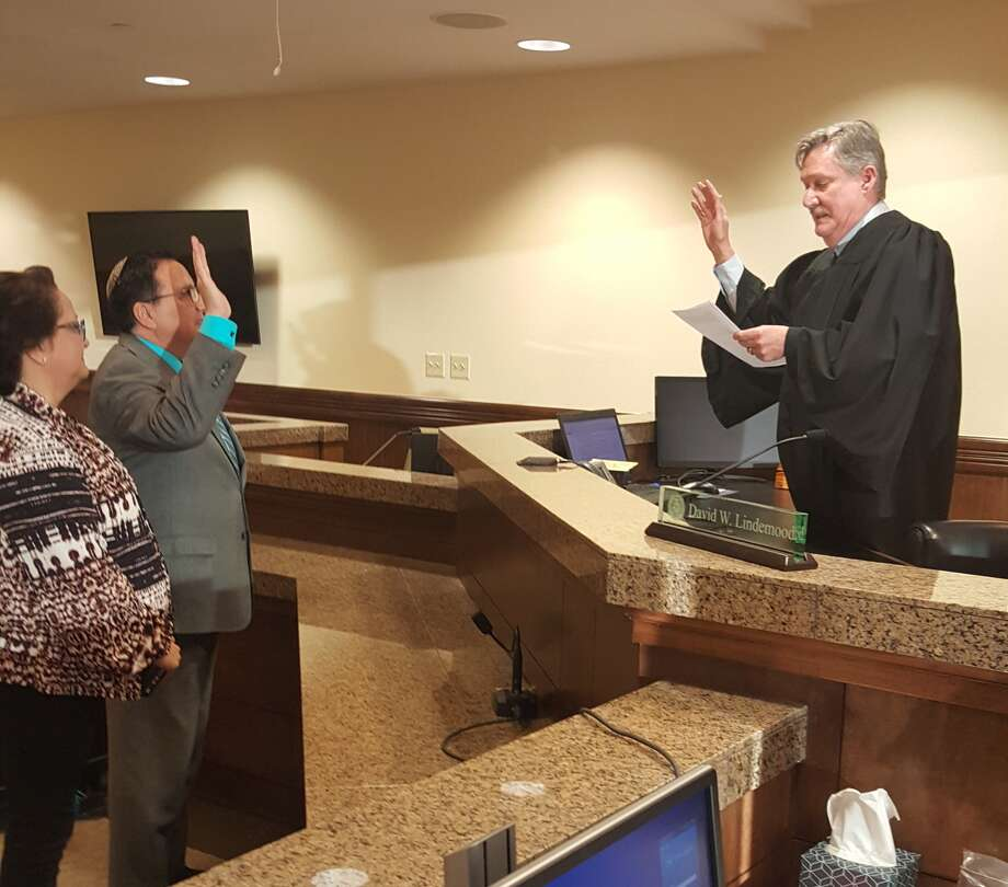 District Judge David Lindemood administers the oath of office to Alex Archuleta, who was named district clerk on Friday. He replaces Ross Bush, who resigned two weeks ago. Photo: Courtesy Photo