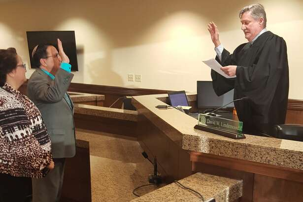 District Judge David Lindemood administers the oath of office to Alex Archuleta, who was named district clerk on Friday. He replaces Ross Bush, who resigned two weeks ago.
