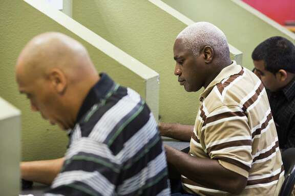Area residents work in cubicles to fill out job applications during a second-chance job fair at Workforce Solutions Alamo in San Antonio. Low unemployment means companies are more willing to consider applicants they formerly would have turned away.