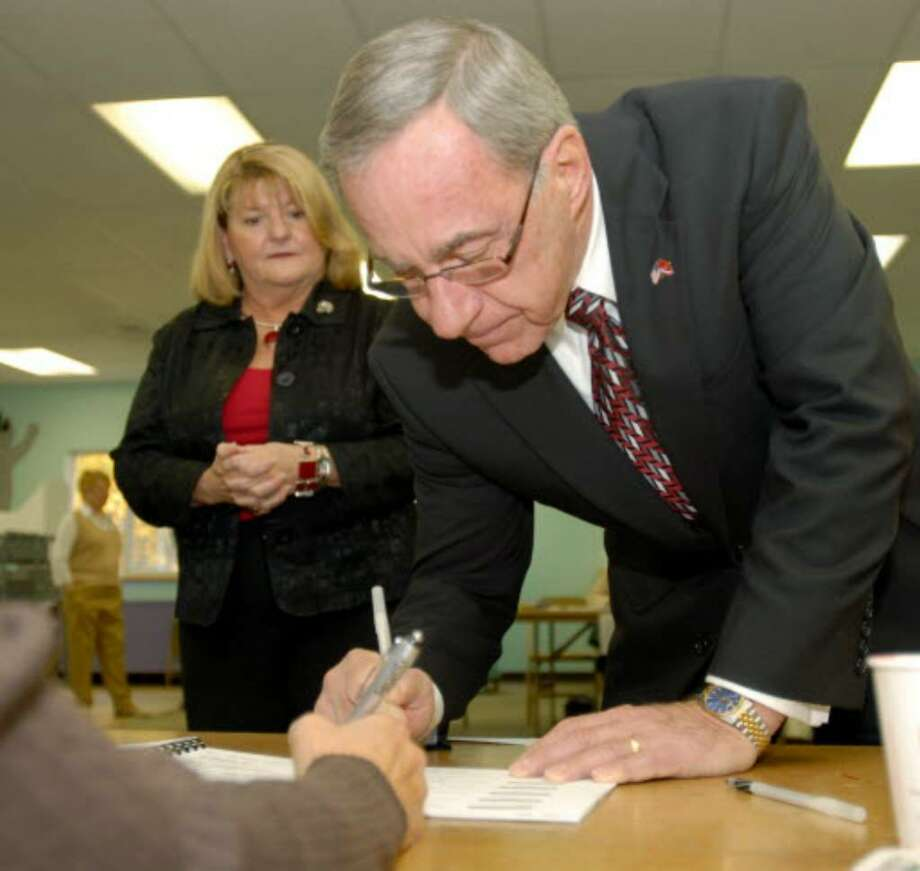 Karen Hoblock, left, watches as her husband and Colonie town supervisor candidate Michael Hoblock signs in to vote today. Hoblock. a Republican, is running against the incumbent, Paula Mahan, a Democrat. (Luanne M. Ferris / Times Union)