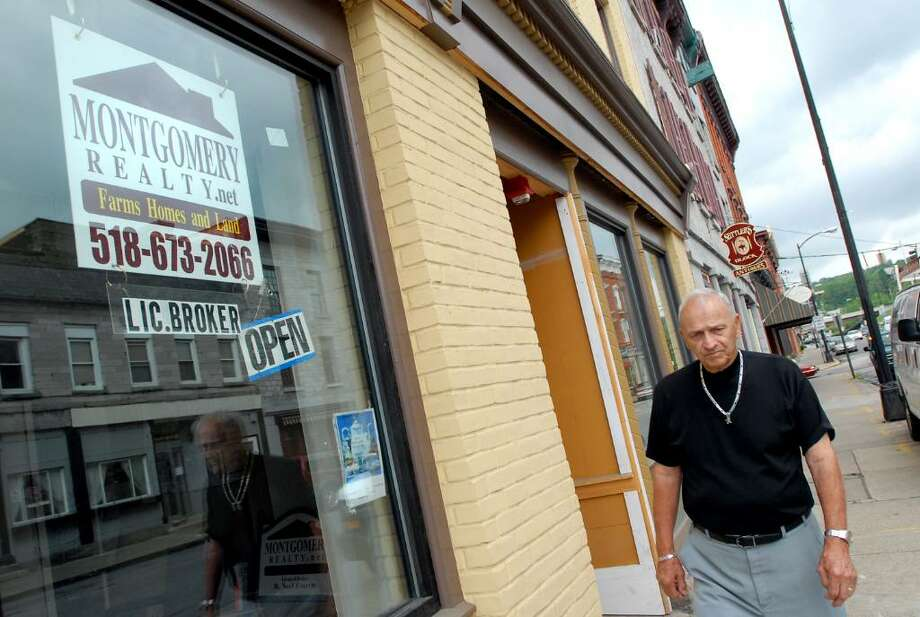 "Mayor Leigh Fuller walks past empty storefronts ton Tuesday, June 1, 2010, in Canajoharie, N.Y. He said business and residents are leaving along with Beech Nut.  ""We with them all the luck in the world,"" said Fuller, ""but what about Canajoharie?"" (Cindy Schultz / Times Union) Photo: CINDY SCHULTZ / 00008921A"
