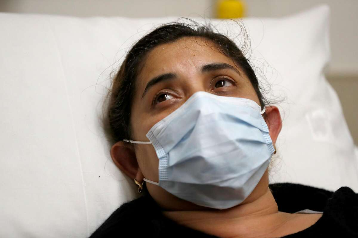 Adriana Gudinoperez, a patient with flu symptoms, looks up after being given ibuprofen in the emergency room at St. Joseph's Hospital in Orange.