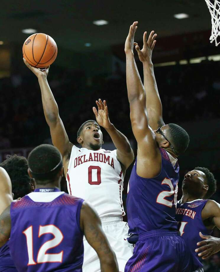 Oklahoma guard Christian James (0) shoots between Northwestern State guard Jalan West (12), forward Ishmael Lane (20) and forward Brandon Hutton, right, in the second half of an NCAA college basketball game in Norman, Okla., Tuesday, Dec. 19, 2017. Oklahoma won 105-68. (AP Photo/Sue Ogrocki) Photo: Sue Ogrocki, STF / AP2017