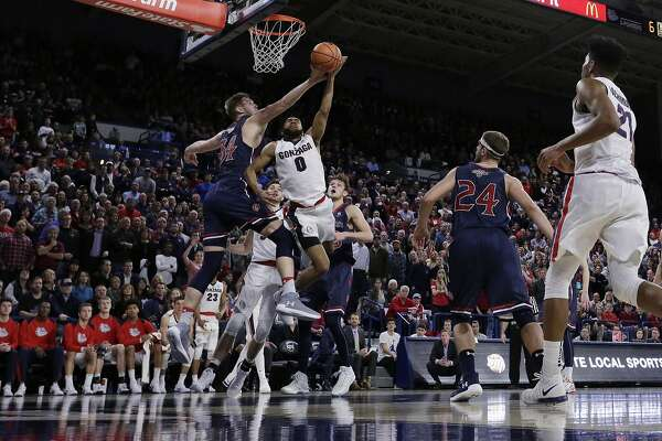 Saint Mary's center Jock Landale, left, blocks a shot by Gonzaga guard Silas Melson (0) during the second half of an NCAA college basketball game in Spokane, Wash., Thursday, Jan. 18, 2018. (AP Photo/Young Kwak)