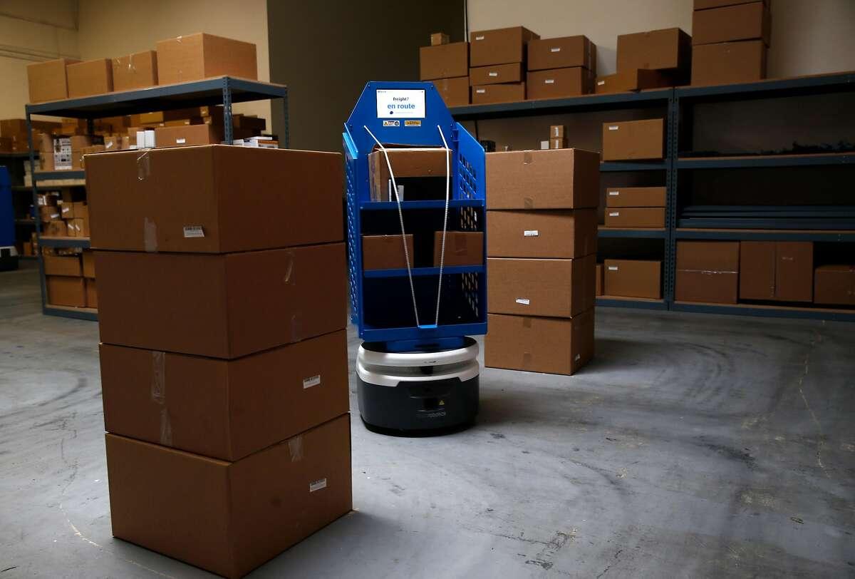 An autonomous mobile robot moves through the Fetch Robotics testing warehouse in San Jose, Calif. on Friday, Dec. 8, 2017.
