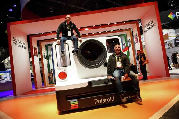 Attendees sit on top of a model of a Impossible BV Polaroid Original OneStep 2 camera at the 2018 Consumer Electronics Show in Las Vegas on Jan. 11, 2018. (