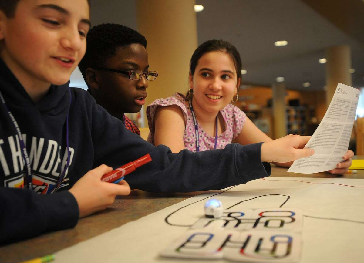 From left; Sixth graders Justin Zarra, 12, Jason Hutchinson, 11, and Lily Banks, 11, experiment with an Ozobot programmable robot for the first time during library learning time at Perry Hill School in Shelton on Tuesday, January 16, 2018. The robot has sensors that respond to specific color codes causing it to speed up, slow down, and change direction.