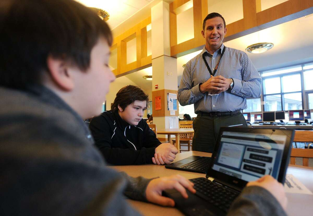 From left; Seventh graders Jeffrey Wojtowicz and Damon Holm, both 12, receive guidance from library media specialist Ron Gydus during library learning time at Shelton Intermediate School in Shelton on Tuesday, January 16, 2018.