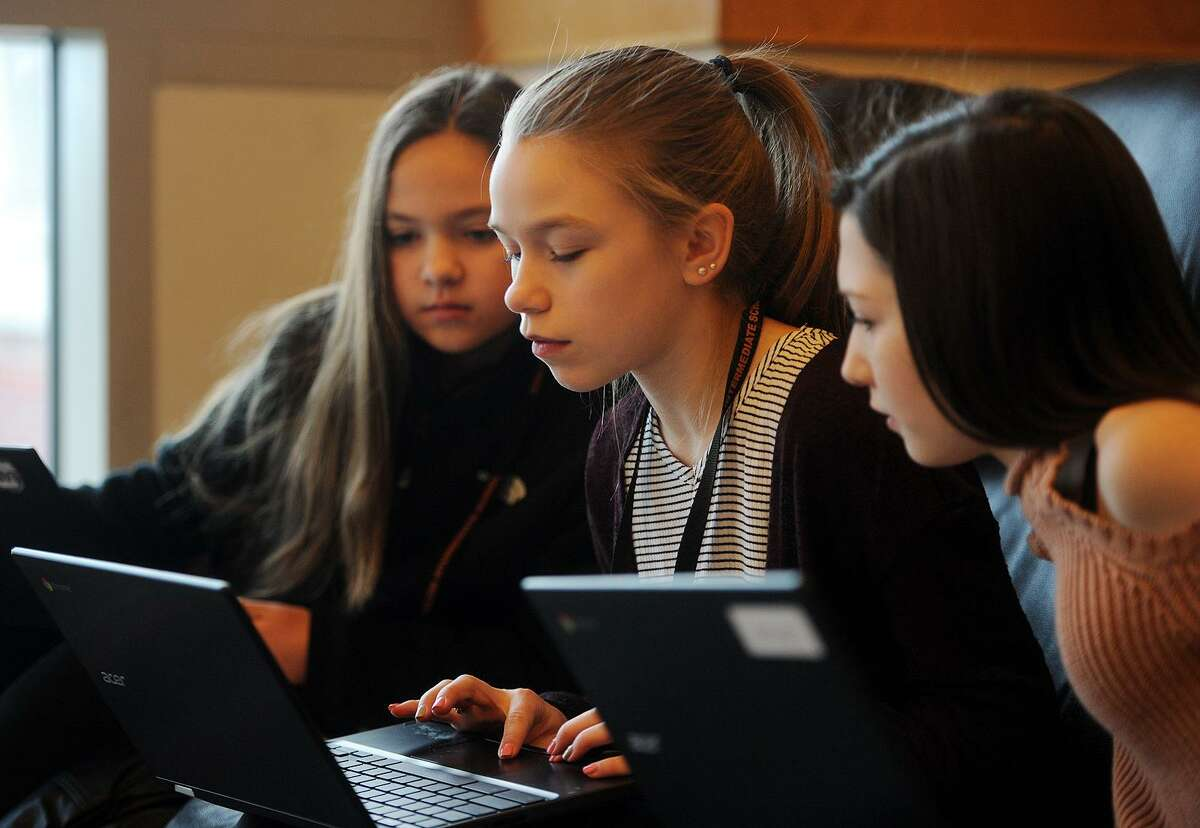 From left; Seventh graders Susie Porto, Katie Bergers, and Ciara Foley, all 12, work on their laptop computers during library learning time at Shelton Intermediate School in Shelton on Tuesday, January 16, 2018.