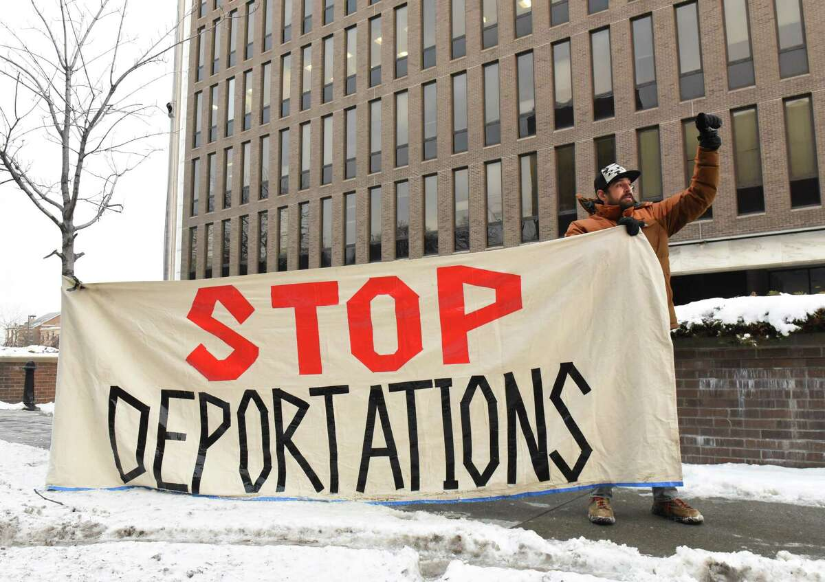 Guillermo Maciel of North Chatham holds a sign while protesters were detained in the lobby of the Leo W. O'Brien Federal Building behind him on Friday, Jan. 19, 2018 in Albany, N.Y. The protesters, members of the Columbia County Sanctuary Movement, were there to occupy Senator Charles Schumer's office. With the possibility of a government shut down, they wanted to send the message to him not to use immigrants as a bargaining chip. (Lori Van Buren/Times Union)