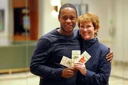 College Assistance Program alum Daniel Maloney, left, poses with Bridgeport Public Education Fund Executice Director Marge Hiller before the start of BPEF's 15th Annual Reunion at the Holiday Inn in Bridgeport, Conn., on Tuesday Jan. 9, 2018. Maloney holds samples of a line of chocolate he produces with his brothers.
