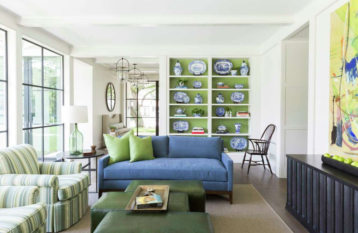 The adults' family room - no toys allowed - in the Tanglewood home of Lucy and Fowler Carter features statement abstract art and shelving backed in a lovely green color that makes blue-and-white pottery pop.
