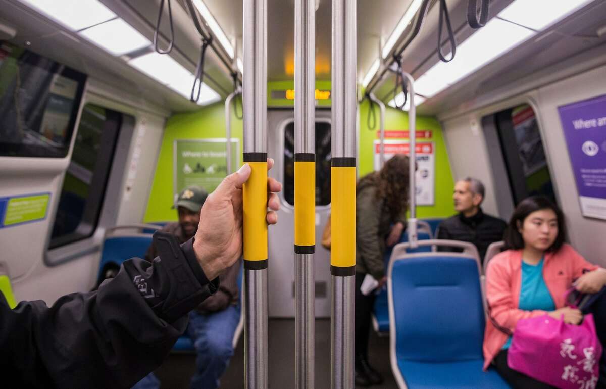 A man holds onto one of the latest additions to Bart's newest train, a group of center poles, during its inaugural ride Friday, Jan. 19, 2018 in Berkeley, Calif.