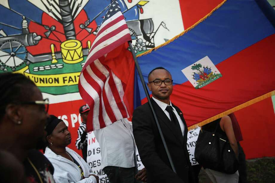 Fandzy Bernadin holds an American flag as he joins with others to mark the 8th anniversary of the massive earthquake in Haiti and to condemn President Donald Trump's reported statement about immigrants from Haiti, Africa and El Salvador on Jan. 12, 2018 in Miami, Florida. Photo: Joe Raedle / / 2018 Getty Images