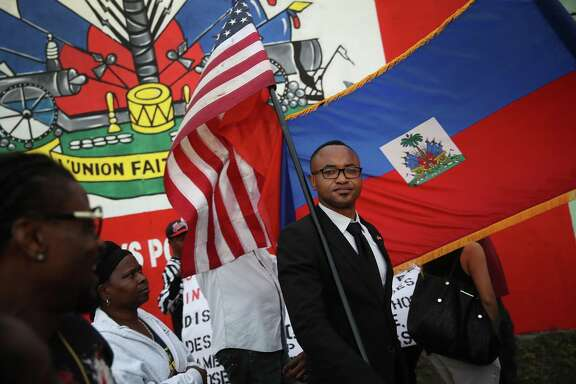 Fandzy Bernadin holds an American flag as he joins with others to mark the 8th anniversary of the massive earthquake in Haiti and to condemn President Donald Trump's reported statement about immigrants from Haiti, Africa and El Salvador on Jan. 12, 2018 in Miami, Florida.