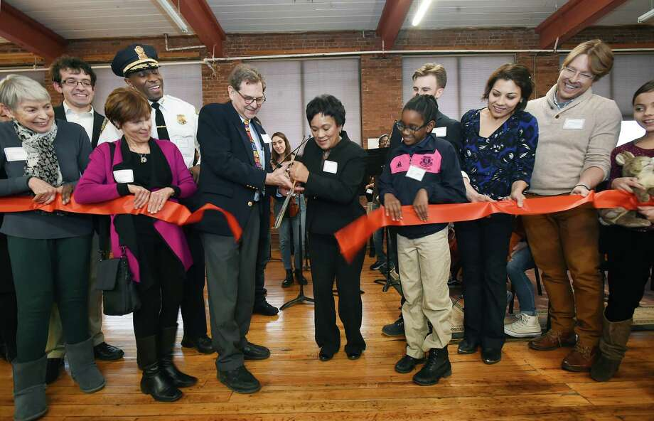 "Co-founder and Board President Marc Mann and Mayor Toni N. Harp cut the ribbon at Music Haven's new 6,700 square-foot state of the art facility at Erector Square at 315 Peck Street, Friday, Jan. 19, 2018, in Fair Haven. Music Haven offers tuition free music instruction to students ages 6-18 who live in the city's ""Promise Zone"" neighborhoods. Also part of the ribbon cutting, from left to right, Laura Altshul, violinist Gregory Tompkins, Wendy Marans, Chief Anthony Campbell, student violaist Jasmine King, 9, violinist Patrick Doane, violinist Yadira Matyakubova, cellist Philip Boulanger, and student cellist Olivia Zlabys, 10. Photo: Catherine Avalone, Hearst Connecticut Media / New Haven Register"