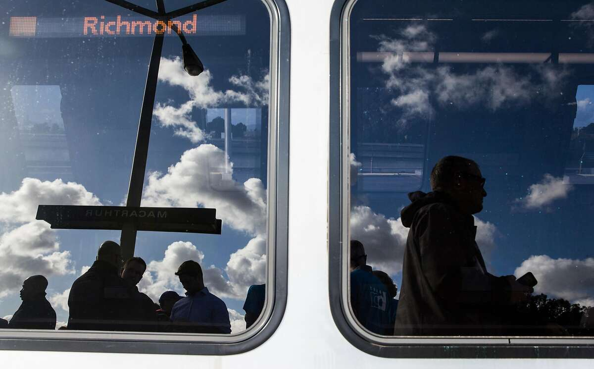 Riders are reflected in the windows of Bart's newest train of their latest fleet during its inaugural ride Friday, Jan. 19, 2018 at MacArthur Station in Oakland, Calif.