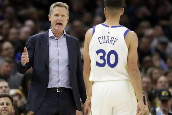 Golden State Warriors head coach Steve Kerr, left, talks with Stephen Curry in the second half of an NBA basketball game against the Cleveland Cavaliers, Monday, Jan. 15, 2018, in Cleveland. (AP Photo/Tony Dejak)
