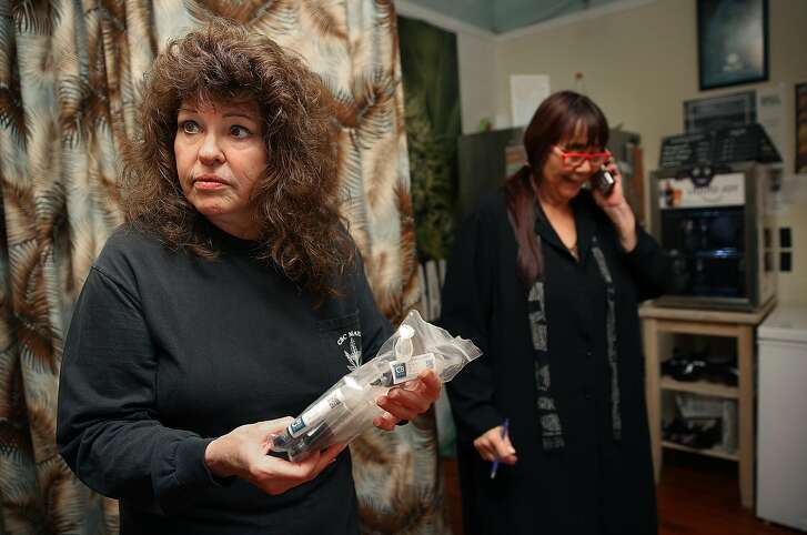 Founder Lynette Shaw shows a customer syringes at the Marin Alliance for Medical Marijuana on Friday, November 10, 2017, in Fairfax, Calif.